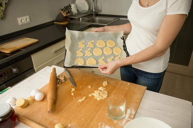 Close-upfoto van een jonge vrouw die een dienblad met koekjes vasthoudt en in de oven zet