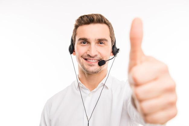 Close-upfoto van een knappe agent die cliënten raadpleegt aan de telefoon die duim omhoog gebaart