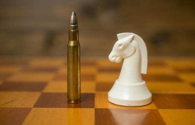 Close-upfoto van een kogel die op een schaakbord staat met een ander schaakstuk