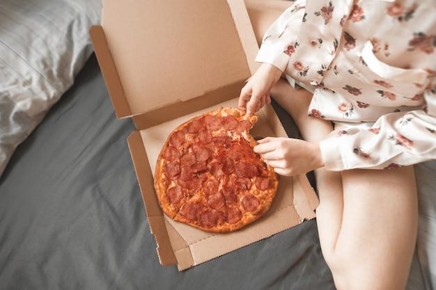Close-upfoto van een meisje in een pyjama zit op het bed en pakt een stuk pizza uit de doos