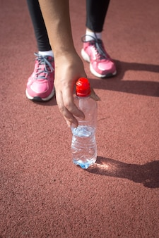 Close-upfoto van een sportieve vrouw die een fles water van de atletiekbaan neemt