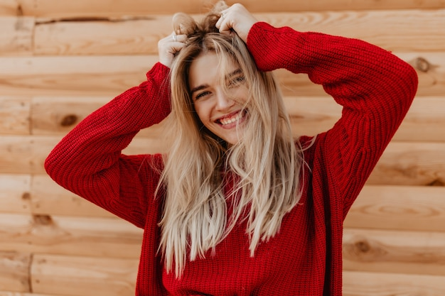Close-upfoto van een verbluffende blonde die vreugdevol op de houten muur glimlacht. mooi meisje in een rode trui buiten gelukkig gevoel.