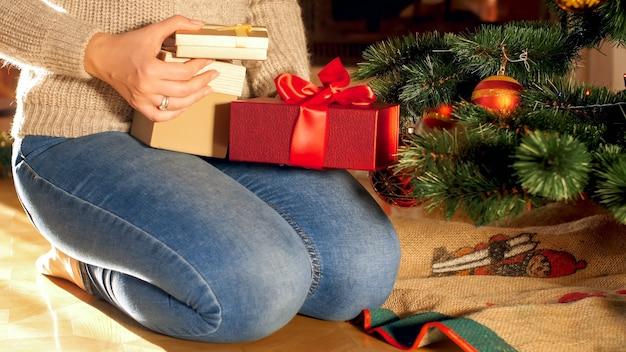 Close-upfoto van een vrouw die op de vloer zit en kerstcadeaus en cadeautjes onder de kerstboom legt