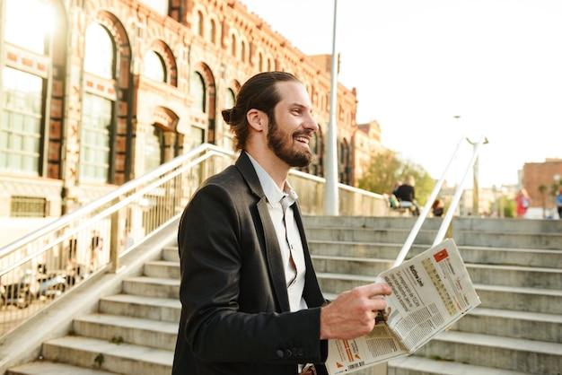 Close-upfoto van europese glimlachende man 30s in formeel kostuum, die in stadsstraat loopt en de krant over economie leest
