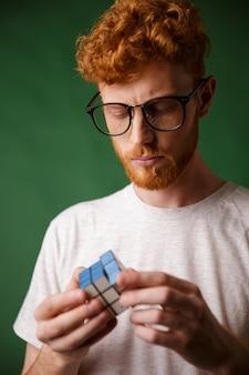 Close-upfoto van geconcentreerde readhead kerel in glazen, die met rubic's kubus spelen