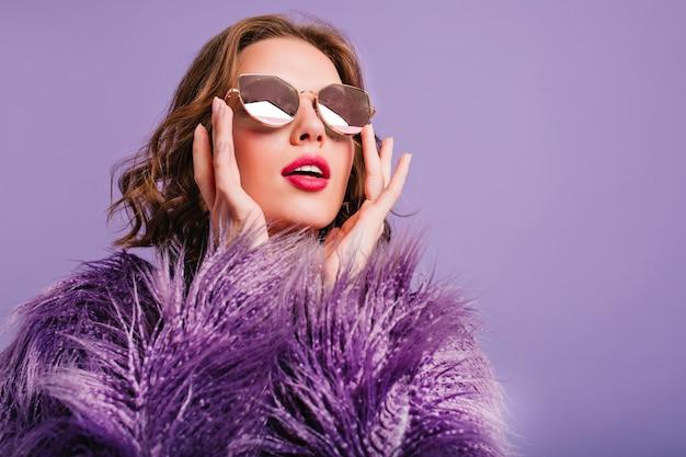 Close-upfoto van geïnspireerde trendy dame die in fonkelingsglazen met open mond omhoog kijkt