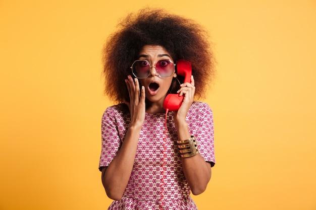Close-upfoto van geschokt retro meisje die met afrokapsel retro telefoon houden