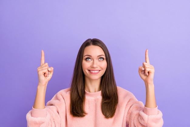 Close-upfoto van geweldige dame die vinger lege ruimte aangeeft, zoekt geen paarse muur op