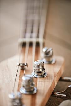 Close-upfoto van gitaarkop met sleutels voor het aanpassen van gitaarsnaren