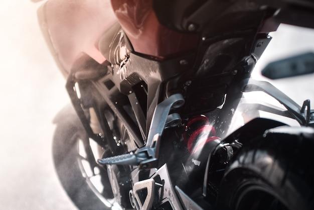 Close-upfoto van het reinigen van de onderdelen van een motorfiets met water onder druk