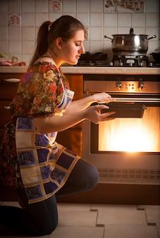 Close-upfoto van huisvrouw die koekjes in oven kookt