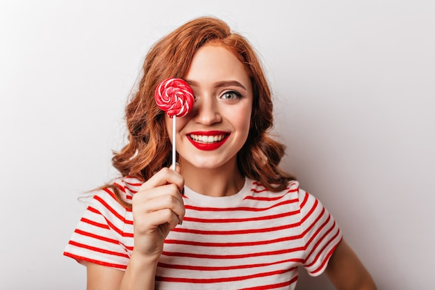 Close-upfoto van jocund-gembervrouw met rood suikergoed. blij europees meisje dat met krullend haar lolly eet.