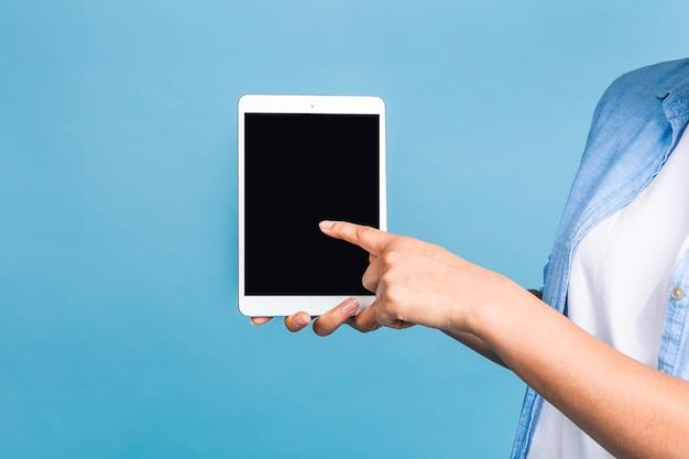Close-upfoto van jong amerikaans studentenmeisje die met krullend afrikaans haar digitale tablet houden en die zich over geïsoleerde blauwe achtergrond glimlachen glimlachen