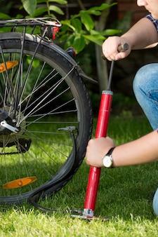 Close-upfoto van jonge man die fietsband pompt
