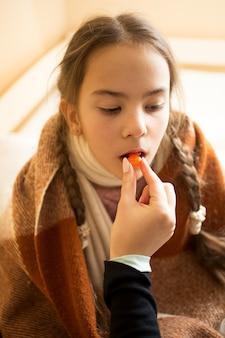 Close-upfoto van jonge moeder die pil geeft aan zieke dochter
