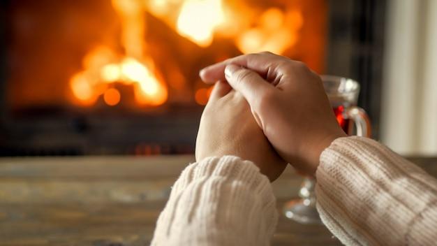Close-upfoto van jonge vrouw die handen verwarmt bij de brandende open haard in huis