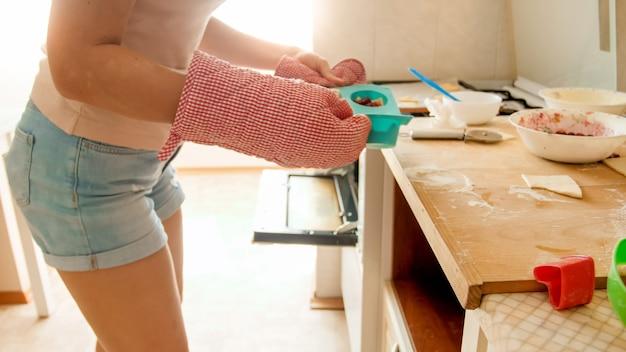 Close-upfoto van jonge vrouw die siliconenvorm met cupcakes in hete oven zet. huisvrouw bakken en koken op keuken thuis at