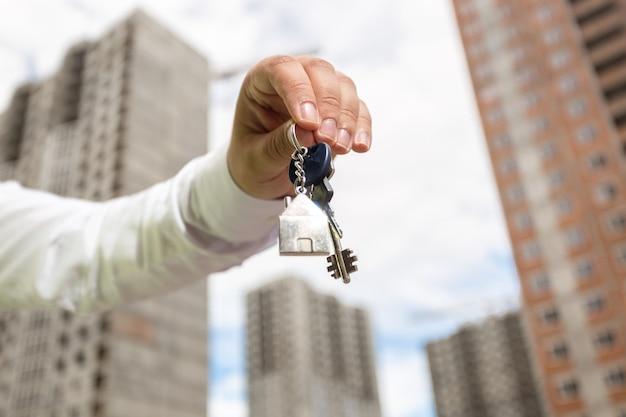 Close-upfoto van jonge zakenmanhand die sleutels van nieuw huis houdt