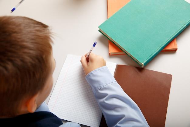 Close-upfoto van leerling die in het notitieboekje tijdens de les schrijft.