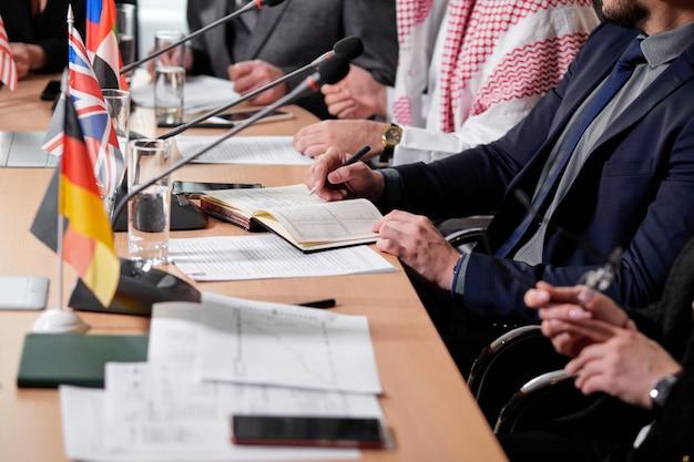 Close-upfoto van leidinggevenden die aan bureau zitten dat notities, met documenten, persconferentie maakt. zakelijke of politieke bijeenkomst in de directiekamer