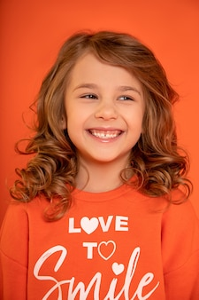 Close-upfoto van leuk mooi kindmeisje 6-7 jaar oud, leidde lachend tegen oranje achtergrond. toothy glimlach. wegkijken.