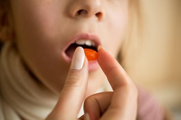 Close-upfoto van meisje dat medicijnen in pil neemt