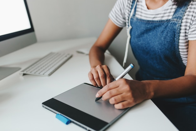 Close-upfoto van meisje met lichtbruine huid die met nieuw apparaat werkt terwijl zij in bureau zit