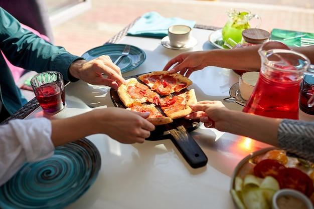 Close-upfoto van mensenhanden die plakjes pizza in koffie nemen