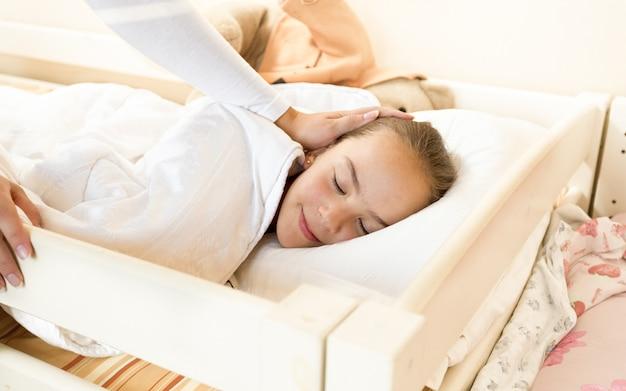 Close-upfoto van moeder die slapende dochter bij bed streelt