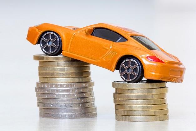 Close-upfoto van nieuwe heldere glanzende gele luxueuze dure stuk speelgoed sportwagen op twee stapels metaal gouden en zilveren muntstukken als symbool van financiële welvaart, rijkdom, voertuigverkoop en aankoop.