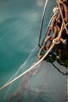 Close-upfoto van oude touwen en roestige meerkettingen op zeewater