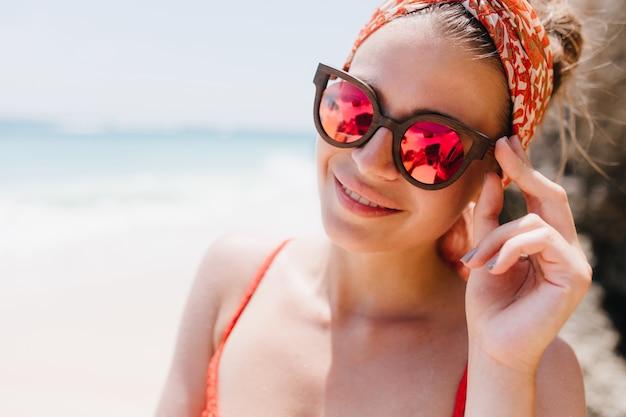 Close-upfoto van prachtige gebruinde vrouw in grote fonkelingsglazen. buiten schot van glimlachend kaukasisch meisje met plezier in zonnige dag op zee.