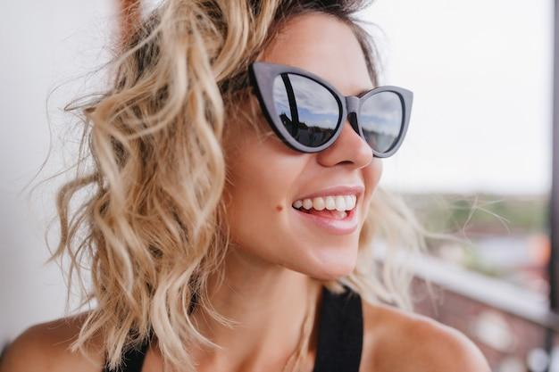 Close-upfoto van prachtige jonge dame met kort blond haar. portret van een prachtig gelooid meisje echte positieve emoties uitdrukken.