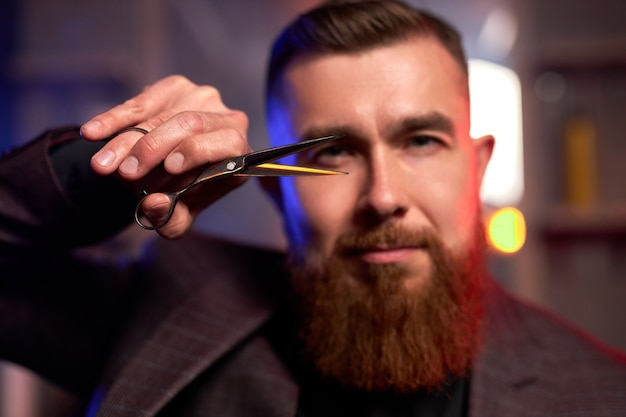 Close-upfoto van schaar in handen van professionele kapper