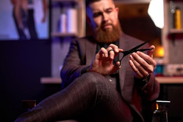 Close-upfoto van schaar in handen van professionele mannelijke kapper