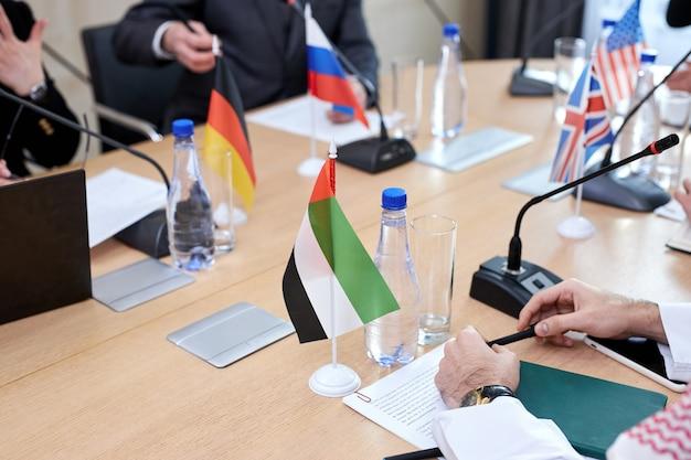 Close-upfoto van tafel en verschillende vlaggen, concept van de internationale topconferentie