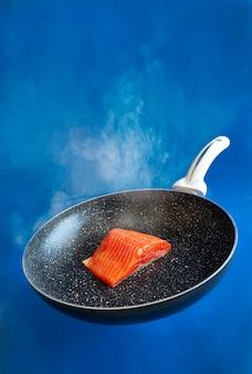 Close-upfoto van verse rauwe zalm, forelfilet op de koekenpan op de blauwe waterachtergrond