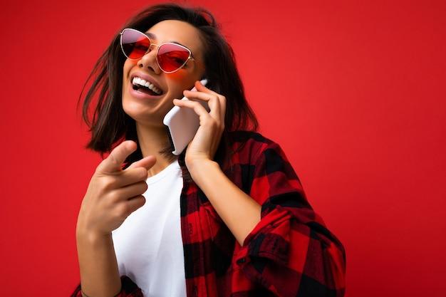 Close-upfoto van vrij gelukkige donkerbruine jongedame, gekleed in stijlvol rood overhemd, wit t-shirt en rode zonnebril
