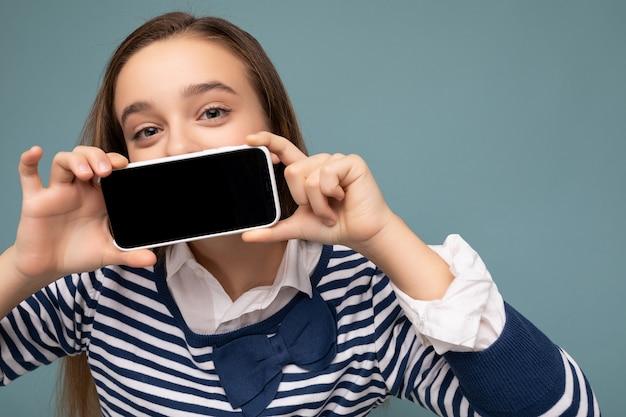 Close-upfoto van vrij positief donkerbruin meisje die gestreepte lange koker dragen status geïsoleerd op blauw