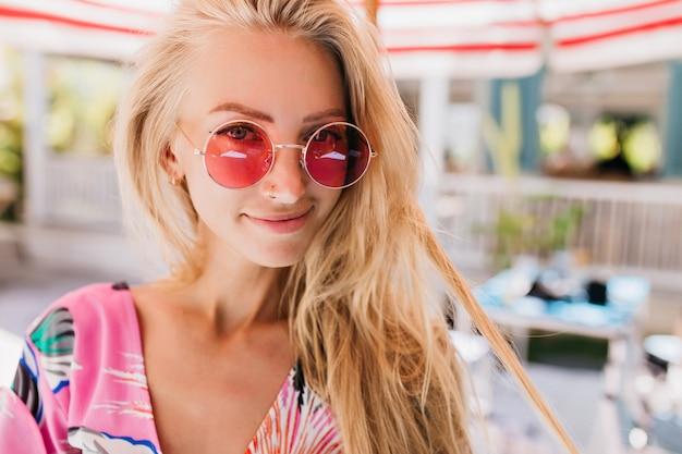 Close-upfoto van vrolijk gelooid vrouwelijk model met lang blond haar. portret van enthousiaste blonde dame in roze zonnebril poseren op onscherpe achtergrond.