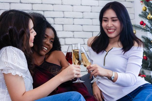 Close-upfoto van vrolijke meisjes die een partij thuis met campagne vieren.