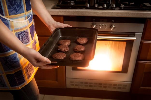 Close-upfoto van vrouw die chocoladekoekjes in hete oven kookt