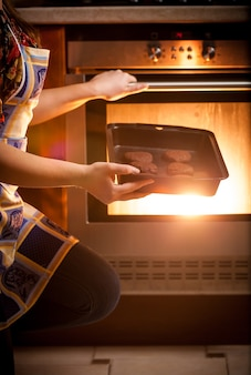 Close-upfoto van vrouw die chocoladekoekjes in oven kookt