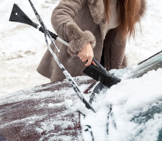 Close-upfoto van vrouw die sneeuw van autokap met borstel schoonmaakt