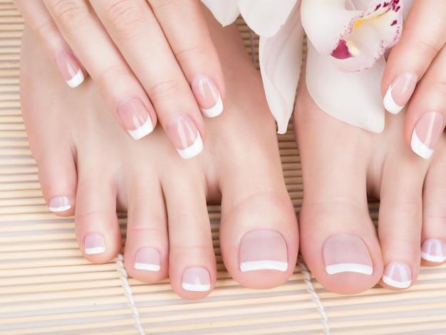 Close-upfoto van vrouwelijke voeten bij kuuroordsalon op pedicure en manicureprocedure - softfocusbeeld