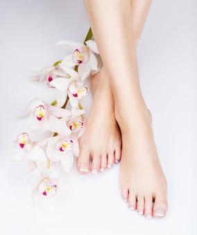 Close-upfoto van vrouwelijke voeten met witte franse pedicure op spijkers