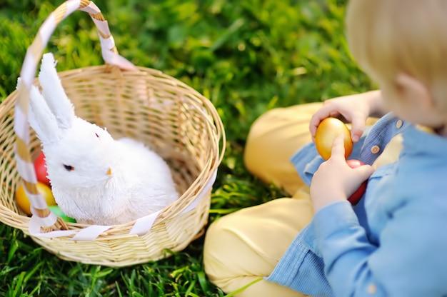Close-upfoto van weinig jongen die voor paasei in de lentepark jacht op pasen-dag