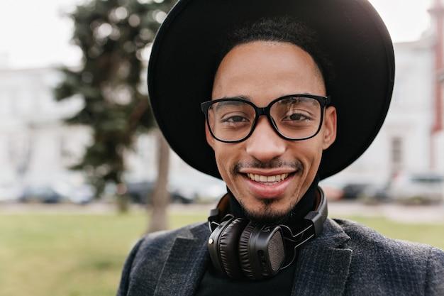 Close-upfoto van zalig afrikaans mannelijk model met donkere ogen die zich op onscherpte aard bevinden. outdoor portret van stijlvolle man in zwarte hoed en koptelefoon lopen op straat.