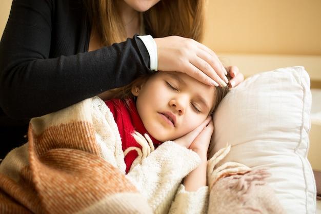 Close-upfoto van zorgzame moeder die het hoofd op het voorhoofd van de zieke dochter houdt