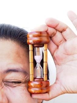 Close-upgezicht van aziatische vrouw met de zandloper van de handholding, tijd om huid en rimpels te behandelen.